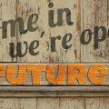 come in we'are open - future. Foto einer Tür mit diesem Spruch darauf.